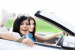 Two happy friends drive the cabriolet Stock Photos