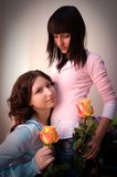 Two happy friends girl with yellow roses Royalty Free Stock Images