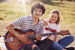 Free Two Happy Friends Have Joyful Expression, Gentle Smiles On Faces, Recreat During Summer Time Outdoor, Play Guitar And Sing Popular Stock Photo - 119177360