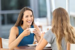 Two happy friends having a casual conversation. Sitting in a bar terrace Royalty Free Stock Image