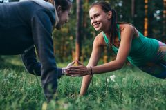 Two happy friends holding hands while doing plank exercise in park.  royalty free stock image