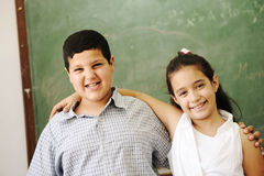Two Happy Friends In Front Of Green Classroom Boar Royalty Free Stock Image
