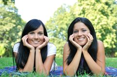 Two happy friends lying outdoors in grass royalty free stock photography