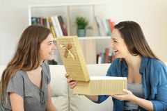 Two happy friends opening a gift box at home. Two happy friends opening a gift box sitting on a couch in the living room at home Stock Photo