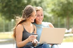 Friends paying online with laptop and credit card stock photo