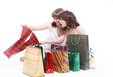 Two happy friends with purchases. It is isolated, a white background Royalty Free Stock Images