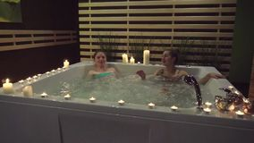 Two happy friends rest in the jacuzzi, saturated with sea salt in the spa center. Two joyful friends chatter in the jacuzzi saturated with sea salt in the spa stock video footage