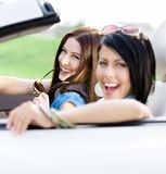 Two happy friends ride the car Stock Images