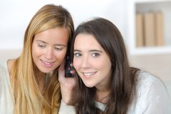 Two happy friends sharing phone Stock Images