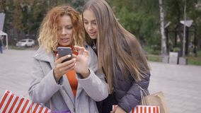 Two happy friends on the street looking at the mobile phone. Couple of fashion women with shopping bags in the city. Leisure together. Girls enjoying their stock video footage