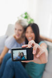 Two happy friends taking photo with camera. At home on couch Royalty Free Stock Photos