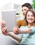 Two happy friends taking photo with tablet pc at home on the cou. Ch Stock Photography