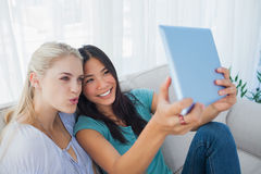 Two happy friends taking photo with tablet pc. At home on the couch Royalty Free Stock Photo