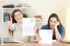Students with approved and falied exams looking at you. Two happy and frustrated students with approved and falied exams looking at you royalty free stock images