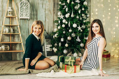 Two happy girl friend opened Christmas gifts. Happy girl opened Christmas gifts near a Christmas tree,preparing for Christmas Stock Image