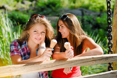 Two happy girl friends eating ice cream outdoors Stock Images
