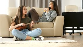 Two happy girl friends having a lot of fun. The youngest is playing at ukulele and the oldest is singing in a microphone stock video footage