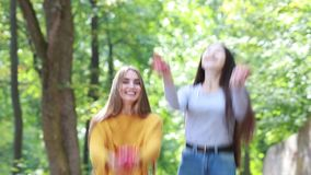 Two happy girl friends with long hair thrown up red rose petals. Two beautiful young girls having fun in the jump throw up red rose petals outdoors in the park stock video footage