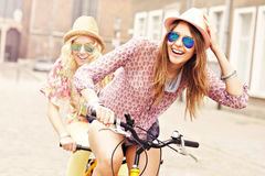 Two happy girl friends riding tandem bicycle Royalty Free Stock Images