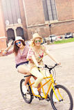 Two happy girl friends riding tandem bicycle Stock Photo