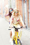 Two happy girl friends riding tandem bicycle Royalty Free Stock Photography