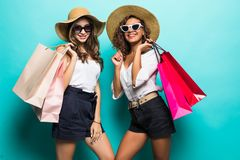 Two happy girl friends in straw hat and sunglasses with shopping bags at blue studio background, copy space, Black friday, sales stock photo