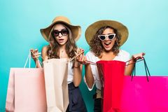 Two happy girl friends in straw hat and sunglasses with shopping bags at blue studio background, copy space, Black friday, sales stock image