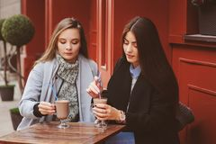 Two happy girl friends talking and drinking coffee in autumn city in cafe. Meeting of good friends, young fashionable students Royalty Free Stock Photos