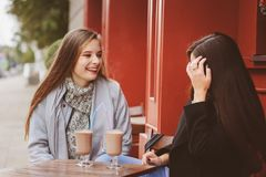 Two happy girl friends talking and drinking coffee in autumn city in cafe. Meeting of good friends, young fashionable students Stock Photography