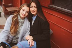 Two happy girl friends talking and drinking coffee in autumn city in cafe. Meeting of good friends, young fashionable students Stock Photos