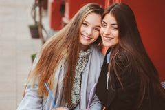 Two happy girl friends talking and drinking coffee in autumn city in cafe. Meeting of good friends, young fashionable students. With natural make up Stock Photography