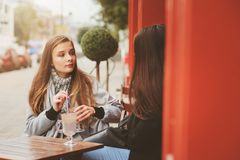Two happy girl friends talking and drinking coffee in autumn city in cafe. Meeting of good friends, young fashionable students Royalty Free Stock Image