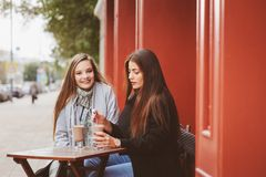 Two happy girl friends talking and drinking coffee in autumn city in cafe. Meeting of good friends, young fashionable students Stock Images