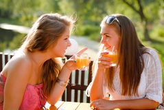 Two happy girl friends in terrace cafe & chatting. Two happy girl friends sitting outdoors in terrace cafe and chatting on the sunny summer day background stock photography