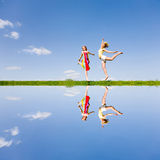 Two happy girl jumping together on green meadow. Two happy girls jumping together on green meadow. Reflected in water Stock Photos