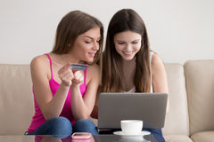 Two happy girlfriend ordering goods in Internet royalty free stock photography