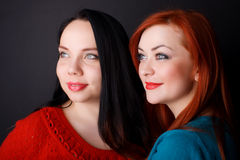 Two happy girlfriends. black background. Two happy young girlfriends brunette and red-hair black background stock photography