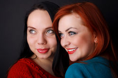 Two happy girlfriends. black background. Two happy young girlfriends brunette and red-hair black background stock images