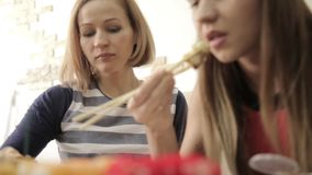 Two happy girlfriends eating sushi in restaurant Japanese cuisine, uses chopsticks.  stock video footage