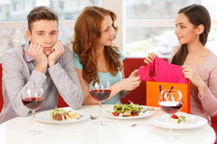 Two happy girlfriends and one sad boy at cafe. Stock Images