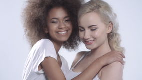 Two happy girlfriends posing on white background. stock video footage
