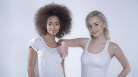 Two happy girlfriends posing on white background. Two girls in casual clothes over white background stock video