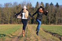 Two happy girlfriends runs hands Royalty Free Stock Photography