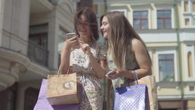 Two happy girlfriends after shopping with shopping bags texting on the cellphone in front of beautiful buildings. Two happy girlfriends after the shopping with stock footage