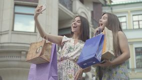 Two happy girlfriends after shopping with shopping bags taking selfie on cellphone outdoors. Leisure of happy girls. Carefree ladies walking through city stock video