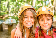 Two happy girlfriends smiling in the adventure park. Wearing helmets Stock Images