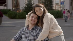 Portrait of disabled happy young man n wheelchair and his wife or friend looking at camera. Caucasian handicapped guy