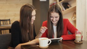 Two happy girlfriends with tablet smile in cafe. Two girlfriends with tablet smile in cafe stock footage