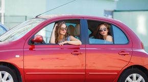 Two happy girlfriends are traveling in the car Stock Photos