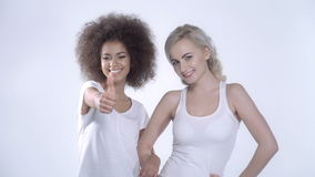 Two happy girlfriends on white background. Two cheerful girls in casual clothes over white background.  Beautiful 20s girls smiling with thumb up and blinking stock video